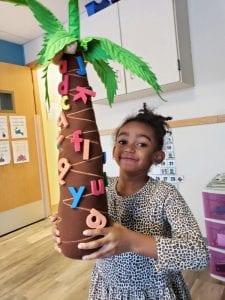 prek girl holding tree
