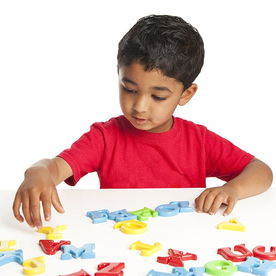 boy playing with letters at preschool