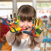 girl with paint on hands at child care center