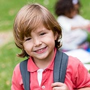 prek boy with backpack at child care center