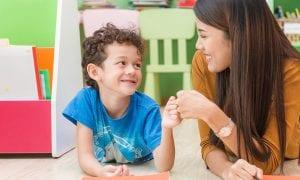 teacher helping student at preschool