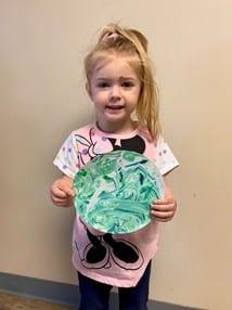 Girl holding earthday art at preschool