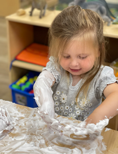 girl playing with shaving cream